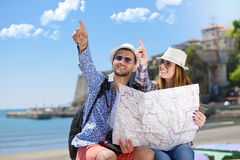 Summer holidays, dating and tourism concept - smiling couple in sunglasses with map in the city Royalty Free Stock Photos
