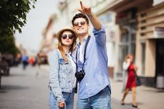 Summer holidays, dating and tourism concept - smiling couple in sunglasses with map in the city, man pointed on direction Stock Image