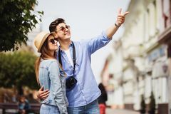 Summer holidays, dating and tourism concept - smiling couple in sunglasses with map in the city, man pointed on direction Stock Photo
