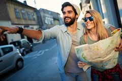 Summer holidays, dating and tourism concept. Smiling happy couple with map in the city. Summer holidays, dating and tourism concept. Smiling couple with map in royalty free stock photo
