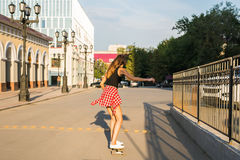 Summer holidays, extreme sport and people concept - happy girl riding modern skateboard on city street Royalty Free Stock Photography