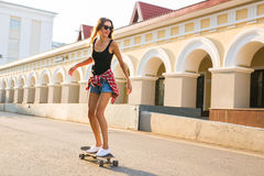 Summer holidays, extreme sport and people concept - happy girl riding modern skateboard on city street Royalty Free Stock Images