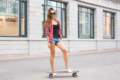 Summer holidays, extreme sport and people concept - happy girl riding modern skateboard on city street Stock Photography