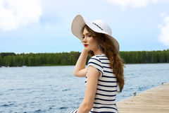 Summer holidays girl on the lake white hat Royalty Free Stock Photography