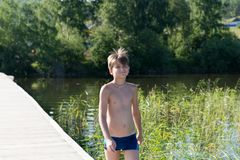 Happy boy 11 years old goes swimming on a wooden pier, on the background of the shore and the lake on a summer sunny day. Summer holidays. Happy boy 11 years old royalty free stock photos