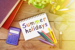 Summer holidays inscription with crayons and notepad on the wooden table. Summer holidays inscription with colored crayons and notepad on the wooden table stock photos