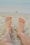 Summer holidays, legs close-up on a background of the sea. Men's feet in the sand, beach photos Stock Photography