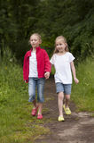 Summer holidays: Littel girls walking on a path in the woods Royalty Free Stock Image