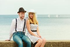 Loving couple retro style dating on sea coast. Summer holidays love relationship and dating concept - romantic playful couple retro style flirting on sea shore Royalty Free Stock Images