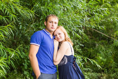 Summer holidays, love, romance and people concept - happy smiling young couple hugging outdoors Stock Images