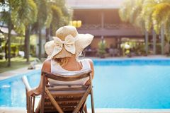 Summer holidays in luxury hotel, woman relaxing in deckchair. Summer holidays in luxury hotel, woman relaxing near beautiful swimming pool Stock Photography