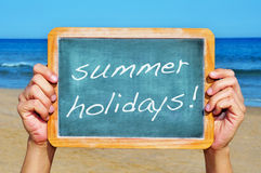 Summer holidays. Man hands holding a chalkboard on the beach with the text summer holidays written in it Stock Photos