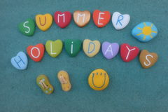 Summer Holidays with multicolored heart stone letters over green sand Stock Photography