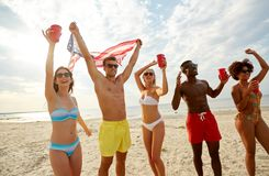 Friends at american independence day beach party. Summer, holidays and people concept - group of happy friends with flag and non-alcoholic drinks celebrating royalty free stock photography