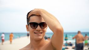 happy smiling handsome young man in sunglasses on beach