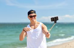 Man with smartphone selfie stick on summer beach. Summer holidays and people concept - happy smiling young man with smartphone selfie stick taking picture on Stock Photography