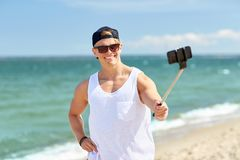 Man with smartphone selfie stick on summer beach. Summer holidays and people concept - happy smiling young man with smartphone selfie stick taking picture on Royalty Free Stock Photography