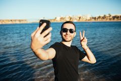 Happy smiling young man in sunglasses victory sign taking selfie on beach. Summer holidays and people concept - happy smiling young man in sunglasses taking Stock Photos