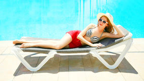 Summer holidays - pretty woman lying on a deckchair. Over a blue water pool background Royalty Free Stock Image