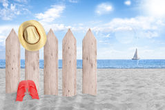 Summer holidays, relax on sand. Summer beach, fence, straw hat, sailing on the horizon Royalty Free Stock Photography