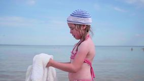 A girl on the beach wipes the body with a towel after bathing. Summer holidays, rest by the sea. Summer holidays, rest by the sea. A girl on the beach wipes the stock video footage