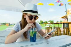 Summer holidays, rest. Teenage girl of 16 years in hat and sunglasses with blue lemonade sits at table in summer street cafe. stock photo