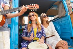 Happy hippie friends playing music in minivan. Summer holidays, road trip, travel and people concept - happy young hippie friends with guitar and tom-tom drum Royalty Free Stock Image