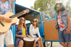Happy hippie friends playing music in minivan. Summer holidays, road trip, travel and people concept - happy young hippie friends with guitar and tom-tom drum Stock Photos