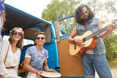 Happy hippie friends playing music in minivan. Summer holidays, road trip, travel and people concept - happy young hippie friends with guitar and tom-tom drum Royalty Free Stock Photography