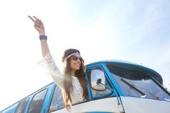 Happy hippie woman showing peace in minivan car Royalty Free Stock Images