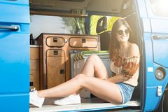 Summer Holidays. Road trip, travel and people concept, young woman resting in minivan car Stock Photos