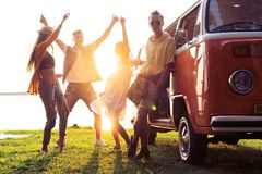 Summer holidays, road trip, vacation, travel and people concept - smiling young hippie friends having fun over minivan. Friends dancing in the light of sunset stock photos