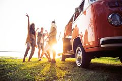Summer holidays, road trip, vacation, travel and people concept - smiling young hippie friends having fun over minivan. Friends dancing in the light of sunset royalty free stock photos