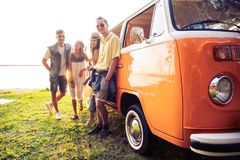 Summer holidays, road trip, vacation, travel and people concept - smiling young hippie friends having fun over minivan. Car royalty free stock image