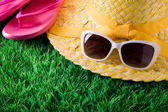 Summer holidays. Sunglasses, straw hat and pink fli flops on lush green grass, vacations concept Royalty Free Stock Photos