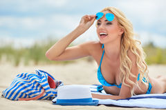 Summer holidays, vacation and beach concept. Girl in bikini and shades on the beach Royalty Free Stock Image