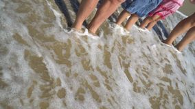 Summer holidays, Vacation concept. Happy Family: father, mother, dauther, son standing on sandy beach in water. spum sea. Water foam on a beach stock footage