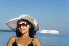 Summer holidays and vacation concept. Girl in bikini sitting on the beach with cruiser at background Stock Photo