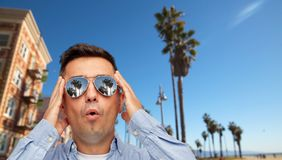 Surprised man in sunglasses over venice beach royalty free stock image