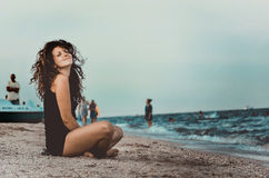 Summer holidays and vacation - girl sitting on the beach. Pretty teenage girl sitting on the beach. Summer holidays and vacation - girl sitting on the beach Stock Image