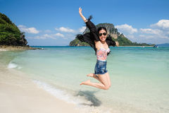 Summer holidays and vacation. Girls jumping on the beach stock images