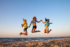 Summer holidays and vacation - girls jumping on Stock Image