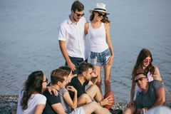 People spending nice time together while sitting on beach, having fun and drinking beer. Summer, holidays, vacation. group of friends having fun on beach royalty free stock images