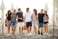 Holidays, vacation. group of friends having fun on beach, walking, drink beer, smiling and hugging. Summer, holidays, vacation. group of friends having fun on royalty free stock photo