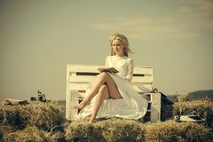 Summer holidays and vacation. Woman reading book on bench on blue sky. Student with camera and typewriter on hay. Girl in straw wreath and white dress on sunny royalty free stock images