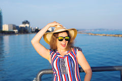 Summer holidays, vacation, travel and people concept - smiling laughing young woman wearing sunglasses and hat on beach. Over sea background Royalty Free Stock Images