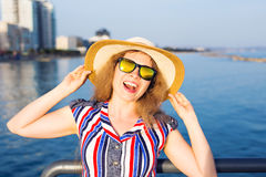 Summer holidays, vacation, travel and people concept - smiling laughing young woman wearing sunglasses and hat on beach. Over sea background Stock Photos