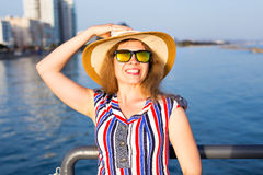 Summer holidays, vacation, travel and people concept - smiling laughing young woman wearing sunglasses and hat on beach. Over sea background Royalty Free Stock Photo