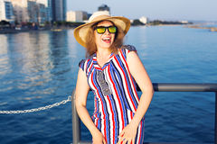 Summer holidays, vacation, travel and people concept - smiling laughing young woman wearing sunglasses and hat on beach Royalty Free Stock Photography