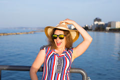 Summer holidays, vacation, travel and people concept - smiling laughing young woman wearing sunglasses and hat on beach Royalty Free Stock Images